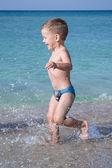 Chico guapo de niño de tres años se ejecuta en el mar — Foto de Stock