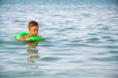 Happy boy enjoying swimming in sea with rubber ring — Stock Photo