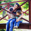 Little boy with his mother sitting on the bridge by the pond — Stock Photo