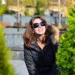 Young beautiful woman in sunglasses in autumn looking on sun — Stock Photo
