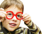 Cute little boy looking through toy red glasses — Stock Photo
