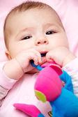 Newborn girl graws toy — Stock Photo