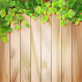 Green leaves on a wood texture. Vector background — Stockvector