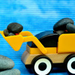 Foto Stock: Yellow tractor toy loaded with stone
