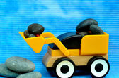 Yellow tractor toy loaded with stone — Stock Photo