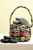 Recycled basket loaded with river stone — Stock Photo