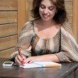 Woman writing something to the notebook using pen — Foto de Stock