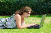 Woman with laptop on the green grass — Foto de Stock