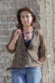Beautiful woman against stone wall — Stock Photo
