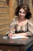 Mulher escrever algo para o notebook usando a caneta — Fotografia Stock