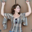 Woman holds iron rings on wooden doors — Stock Photo #37124425