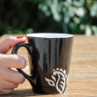 Hand holding big black coffee mug — Stock Photo
