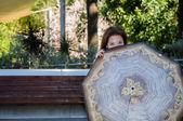 Uma mulher atraente, a espreitar por trás de um guarda-chuva — Fotografia Stock