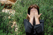 Portrait of a young woman covering face with hands — Stock Photo