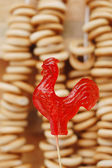 Red sugar cockerel on a stick with bagels on background — Stock Photo
