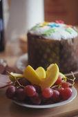 Frutta e torta celebrativa di pasqua decorate con fiori di zucchero e croce — Foto Stock