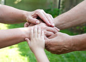 Family holding hands together outdoor — Stock Photo
