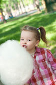 Girl eating cotton candy — Stock Photo