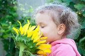 Beautiful little girl and sunflower — Stock Photo