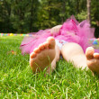 Happy little girl lying on green grass — Stock Photo