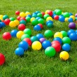Foto Stock: Heap of Colorful Balls on green grass