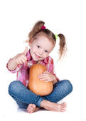 Little girl with pumpkin thumbs up — Stock Photo