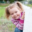 Cute little girl is playing hide and seek outdoors — Stock Photo