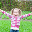 Open arms little happy girl green meadow — Stock Photo