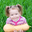 Cute little girl on the meadow with pumpkin — Stock Photo