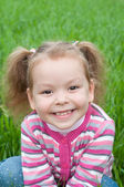 Cute smiley little girl on the meadow — Zdjęcie stockowe