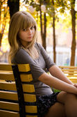 Girl on a bench in a park — Stock Photo