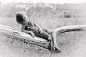Black and white shot of a girl on a log. — Stock Photo