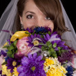Bride peeking over flowers — Stock Photo #12473268