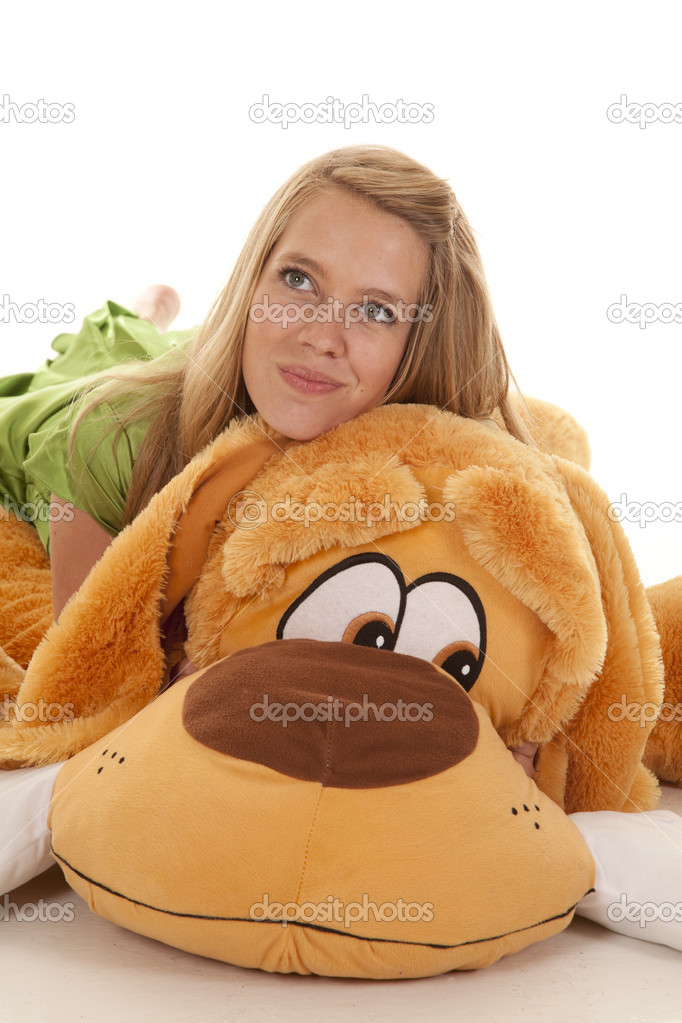 A teen girl laying on her stuffed dog with a smile on her face — Stock Photo #12497714
