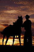 Cowboy holding horse in sunset — Stock Photo