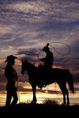 Cowboy on horse swinging rope — Stock Photo