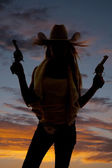 Woman silhouette two guns — Stock Photo