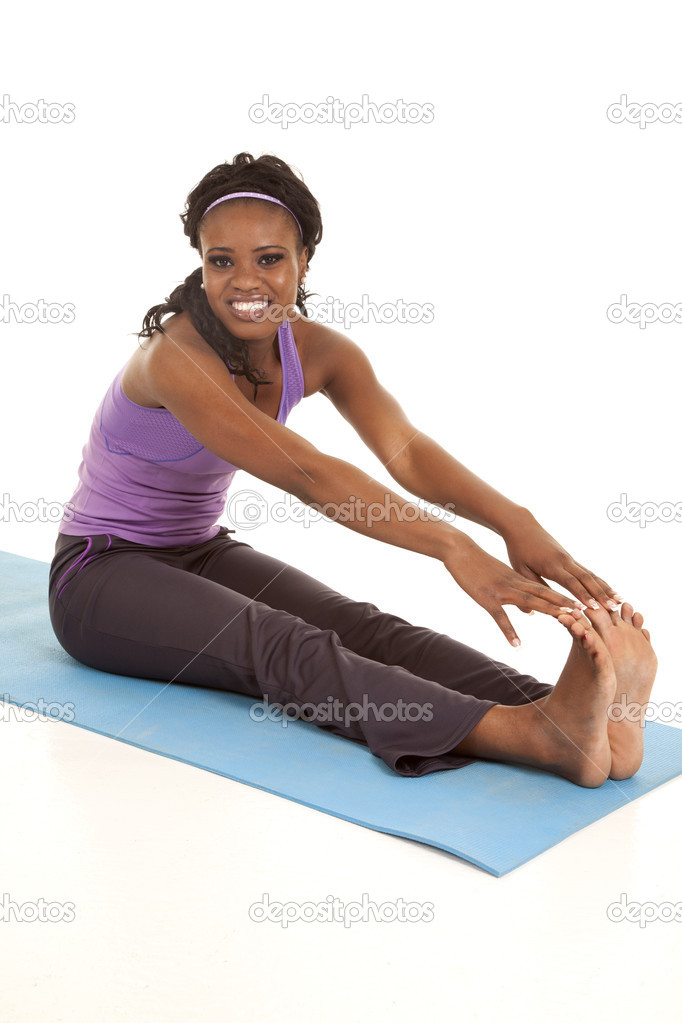 A woman sitting on her mat stretching out her legs with a smile on her face.  Stock Photo #13744378