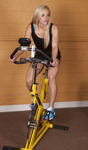 Woman gym bike look side — Stock Photo