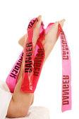 Woman legs sheet danger tape — Stock Photo