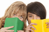 Two girls looking from behind books — Stock Photo