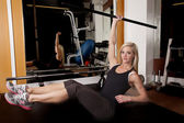 Gym femme s'asseoir jambes barre vers le haut — Photo