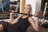 Woman gym sit up bar at chest — Stock Photo