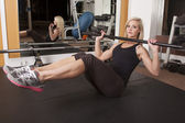 Woman gym sit up with bar — Stock Photo