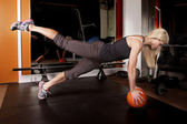 Woman in gym push up leg up ball — Stock Photo