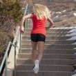 Woman red tank run up stairs snow — Stock Photo