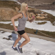 Woman run by in snow gray tank — Stock Photo #22525709