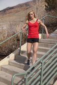 Woman fitness red run down stairs — Stock Photo