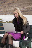 Woman outside snow laptop smile — Stock Photo