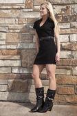 Woman black dress rock wall smile — Stock Photo